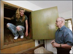 Gail Wahl, left, climbs out from a hidden corner of the old library after exploring it with Mr. Slack.