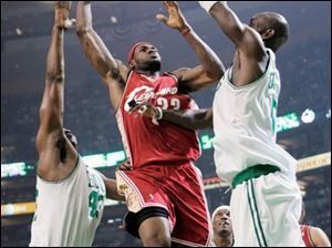 Cleveland's LeBron James shoots between Boston's Kendrick Perkins, left, and Kevin Garnett last night in Boston.