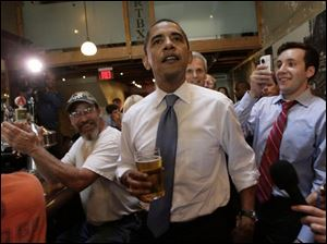 Democratic presidential hopeful, Sen. Barack Obama, D-Ill., holds a glass of beer as he greets people at Raleigh Times bar in Raleigh, N.C., on Tuesday.