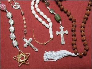 Baha'i prayer beads, left, a Catholic rosary, a Muslim mesbaha, Anglican Protestant beads, and a Hindu mala at the boutique.