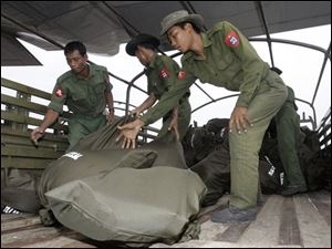 Myanmar soldiers unload bags of supplies aid, donated by Thai King Bhumibol Adulyadej, from a Thai military plane onto a truck at Yangon airport in Myanmar Sunday, May 11, 2008. More food reached Myanmar's hungry cyclone victims as roads were cleared of fallen trees, but a British aid group warned that up to 1.5 million face death if they do not get clean water and sanitation soon.