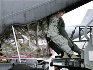Master Sgt. Todd Kneisley, a 1992 graduate of Defiance High School, helps crewmen load relief supplies for Myanmar on a C-130 cargo plane at Utapao Air Base in Thailand. The supplies will be flown to neighboring Myanmar, which was devastated by a cyclone more than a week ago. Sergeant Kneisley, an aerial porter, lives in Guam with his wife and two children, Dan Kneisley, his father, a Defiance resident, said.