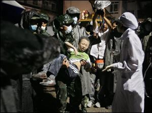 Rescue workers carry out a young boy from the rubble of a collapsed house in Dujiangyan, a close city to the epicenter of the earthquake, in southwest China's Sichuan province on Tuesday. The death toll from a powerful earthquake in China that toppled buildings, schools and chemical plants climbed Tuesday to about 10,000, while untold numbers remained trapped after the country's worst quake in three decades. (ASSOCIATED PRESS)
