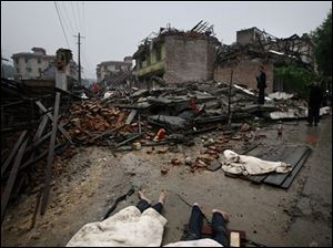 Dead bodies are seen beside the collapsed houses at the earthquake-affected Puyang Township in Dujiangyan of southwest China's Sichuan province Tuesday. 