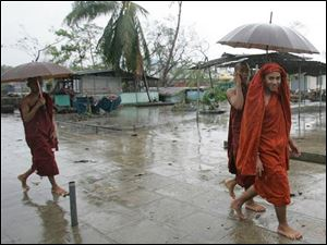 Myanmar Buddhist monks walk in the rain on the outskirts of Yangon, Myanmar on Thursday. (ASSOCIATED PRESS)