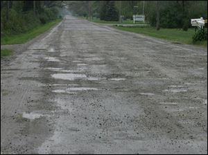 Potholes pepper a three-mile stretch of Rauch Road. Officials are trying to come up with money to make repairs.