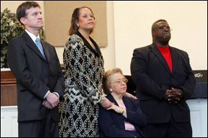 Attorney Thomas Sobecki, left, Crystal Dixon, her mom Nadine Dixon and church Bishop James M. Williams, Sr., gather at a press conference and support rally at End Time Christian Fellowship, in Toledo on Wednesday.