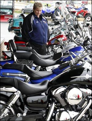Millbury's Donna Young looks at motor scooters at a motorcycle dealership in Maumee.