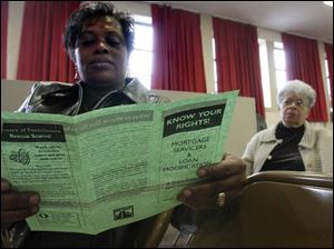 Mary Chavis, left, looks over information as she and Rachel Gibbs of New York City attend a church workshop on surviving the mortgage crisis.