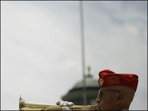 Larry J. Barnett of Temperance, Mich., who served in the U.S. Marine Corps, plays 'Taps' during the unveiling ceremony.