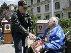 Purple Heart recipients William Sauerwein of Maumee, left, and Leo Uliczny, 91, of Toledo shake hands at a memorial honoring veterans who were awarded the medal. The granite monument, in background, was unveiled at the Civic Center Mall in Toledo.