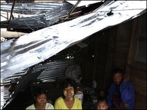 A Myanmar family live in a house which was destroyed by cyclone Nargis on the outskirts of Yangon, Myanmar, Sunday, May 18, 2008. Thousands of children in Myanmar will starve to death in two to three weeks unless food is rushed to them, an aid agency warned Sunday as an increasingly angry international community pleaded for approval to mount an all-out effort to help cyclone survivors.