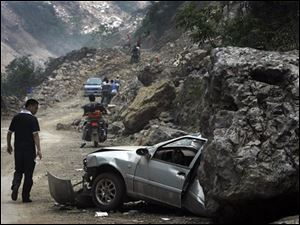 A man looks at a car being half flattened by a huge rock as motorists ride through a damaged road head to Hongkao in Dujiangyan, in southwest China's Sichuan province, Saturday, May 24, 2008. China's earthquake death toll has passed 60,000 and could rise to 80,000 or more, Premier Wen Jiabao said Saturday as he and U.N. Secretary-General Ban Ki-moon visited the disaster area.