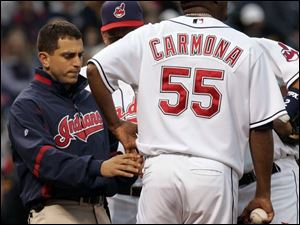 A Cleveland trainer examines Fausto Carmona, who hurt his left hip while covering first base in the third. He left the game.