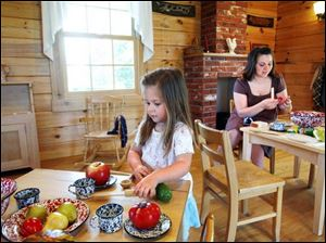 Emilia Braman, 2, and her mother, Autumn, of Battle Creek, Mich., settle into Sauder Village's Little Pioneers Homestead, which includes a cabin and barn with furnishings aimed at the stroller crowd.