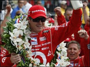 Scott Dixon finally got to hoist the traditional bottle of milk in Victory Lane in Indianapolis after a couple of close misses. (ASSOCIATED PRESS)