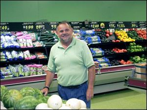 After serving his sentence for bribery, former city councilman Bob McCloskey stacks groceries in Toledo Food Market. As councilman, he said he helped at the store's grand opening.