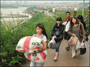 Earthquake survivors carry their belongings to move to higher grounds as the drainage has begun at the swollen Tangjiashan quake lake at Mianyang in southwest China's Sichuan province on Saturday June 7, 2008.