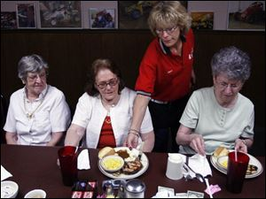 Joyce Gossard serves Kitty McFadden of McComb, Ohio, at the South Side Family Restaurant in Findlay. Ms. McFadden and her friends Alice Bowman, left, and Beverly Stein, right, both of Findlay, participate in a new dining program for seniors.