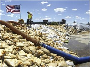 Standing atop a mountain of sandbags, Davenport Street Department employee Don Korch looks over the flooding Mississippi River in downtown Davenport, Iowa on Tuesday.