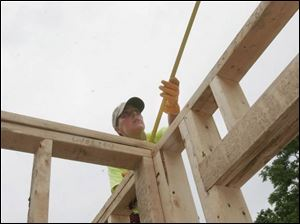 Tressa Duffin of Monroe measures a door frame in a house on Almyra Avenue in Monroe under construction in a Habitat for Humanity 'Blitz Build' on the city's east side.