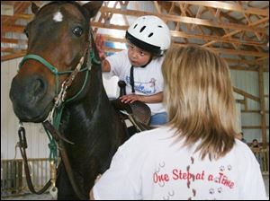 A participant in Serenity Farm's Lucky Riders program pets her steed as Michelle Reiter, a member of the farm's board, helps. The program is intended to boost balance and socialization.