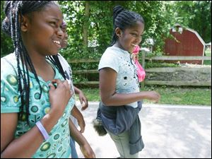 Shaliyah Thompson, left, Tonia Douglas, and Mariah Kyles enjoy the fresh air as they walk three miles on the University Parks Trail.