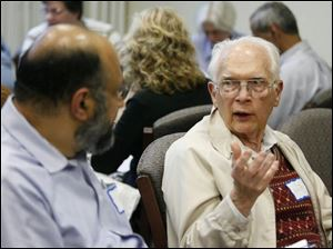 S. Zaheer Hasan, left, a Muslim, talks with Bill Searles, a Unitarian, at the discussion sponsored by WGTE-TV, Channel 30, and the MultiFaith Council of Northwest Ohio.