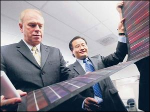 Gov. Ted Strickland examines a solar panel with Xunming Deng of Xunlight Corp. in November,