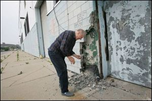Jim Cherry of Harper Woods, Mich., picks up a piece of the crumbling wall at Tiger Stadium, which is being readied for demolition.