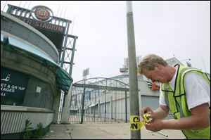 Dan Williamson of Detroit puts caution tape on fencing outside the stadium.  Going to Tiger Stadium was going to a ballpark. Going to Comerica [Park] is like going to the mall,  he said.