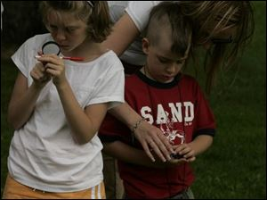NBRW compass03p  06/25/2008  Blade Photo/Lori King  from left: Brooke Robbins, 8, and Ceal Savidge, 6, with his mom, Jennifer Savidge, learn how to use a compass during the compass course challenge at Secor Metropark in Sylvania,  Ohio.