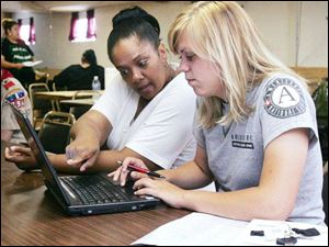Food stamp outreach worker Anita Sanders and Carrie Riddle, an AmeriCorps VISTA member, await clients needing food stamps at Dominion Christian Center.