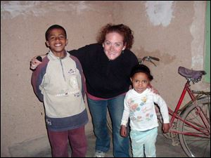 Rebecca Gehring of Toledo, poses with her little 'siblings' from her Moroccan host family, Mohammed, left, and Eham, right, in a village where she served as part of the Peace Corps.