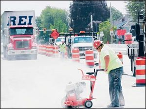 Tod Boose of Smith Paving Inc. of Norwalk, Ohio, cuts new concrete on U.S. 20 on Woodville's west side. On Monday, traffic on U.S. 20 will be shifted over to the 