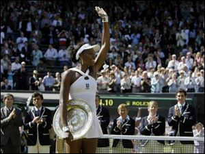 Venus Williams of the US holds her trophy and waves the crowd after winning the women's singles final against her sister Serena on the Centre Court at Wimbledon, Saturday.