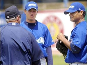 West Michigan Whitecaps players Wilton Garcia, center, and Mauricio Robles, right, talk with a roving hitting coach