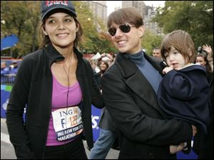 Katie Holmes joins her husband, Tom Cruise, and their daughter, Suri, after Holmes finished the New York City Marathon last November.