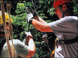 A guide, left, shows writer Mike Kelly how to maneuver on the zipline.