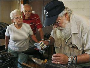 Shirley and Jim Carroll watch Don Witzler's silversmithing work at Providence MetroPark near Grand Rapids by the Isaac Ludwig Mill. Mr. Witzler took up the art about 30 years ago.