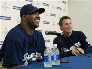 CC Sabathia, left, and manager Ned Yost are all smiles because the big left-hander should help the Brewers' playoff chances.