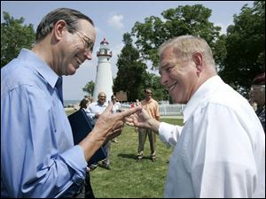 Former Ohio Gov. Bob Taft and present Gov. Ted Strickland joke before the ceremonial signing at Marblehead Lighthouse.