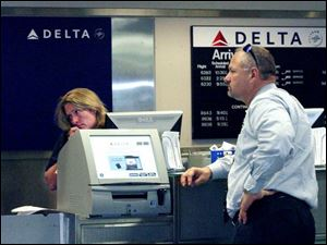 John Zajac of Perrysburg waits as a Delta agent at Toledo Express tries to help him change his daughter s flight from Italy.