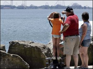 Olivia Matlack, 8, of Northwood takes a closer look at Cedar Point, just across Sandusky Bay from Marblehead. She was visiting the village last week with Mike and Julie Marshall of Millbury, Ohio.