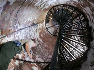 Dianne Rozak, naturalist at Marblehead Lighthouse State Park, climbs the 77 spiral steps to reach the observation deck.