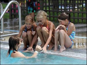 Ann Peltier, 10, cools off in the water while talking to, from left, Molly Musgrave, 7, her sister Abby Musgrave, 9, and Bailee Markowiak, 8, at Pickford Park Aquatic Facility in Toledo. Many public pools reached capacity early in yesterday's heat.