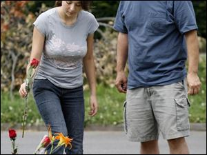 Bianca Salinas, 14, with her father, John, places a rose on an informal memorial to her friend Kenneth Kimble near the corner of Idaho and White streets in East Toledo.