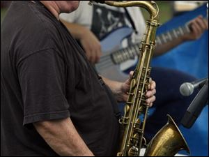 Saxophonist Gene Parker of the Gene Parker Quartet plays some blue notes during this year's blues festival downtown at Festival Park. In addition to music, the waterfront festival also features summer cuisine.