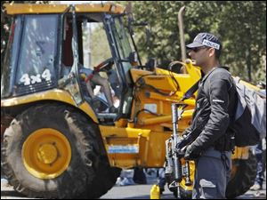 An Israeli security force officer stands guard next to a front-end loader as the Palestinian driver sits dead in his seat at the scene of an attack in Jerusalem on Tuesday.
