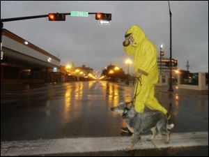 Ren Garcia walks his dog, Buddy, through downtown Brownsville, Texas, as Hurricane Dolly approaches the Rio Grande Valley on Wednesday. (ASSOCIATED PRESS)